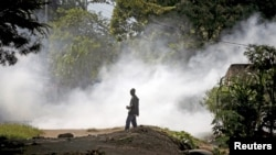 A protester watches after a policeman threw a teargas canister during a protest against Burundi President Pierre Nkurunziza and his bid for a third term in Bujumbura, Burundi, June 2, 2015.