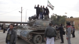 Free Syrian Army fighters pose on a tank after they said they fought and defeated government troops from the town of Ras al-Ain, near the province of Hasaka, 600 kilometers from Damascus, November 22, 2012.