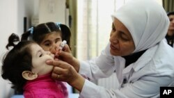 Ma'aikaciyar lafiya tana ba jaririya maganin rigakafin Polio a kasar Syria