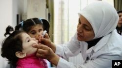 A health worker administers polio vaccine to a child as part of a UNICEF-supported vaccination campaign in Damascus, Syria.