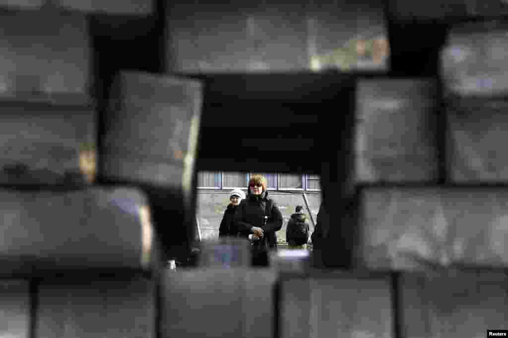 A mourner is seen through a barricade in Kyiv's Independent Square.
