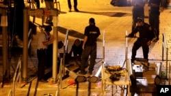 ເຈົ້າໜ້າທີ່ຕຳຫຼວດ ອິສຣາແອລ ຖອດເຄື່ອງກວດຈັບໂລຫະ ຢູ່ນອກບໍລິເວນ ວັດມຸສລິມ al-Aqsa ໃນເຂດເມືອງເກົ່າ ເຈຣູຊາເລັມ. 25 ກໍລະກົດ, 2017.