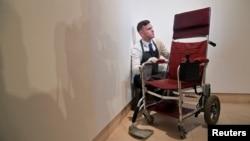 Ahli barang seni Tom Richardson dan kursi roda milik mendiang Stephen Hawking, di balai lelang Christie, London, 30 Oktober 2018