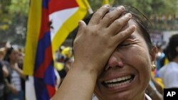 An exile Tibetan woman cries after Jampa Yeshi, a Tibetan self immolated during a protest, in New Delhi, India, FILE March 26, 2012.