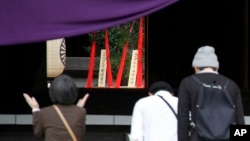 Religious offerings dedicated by Japanese Prime Minister Shinzo Abe are seen, center in the background, as people pray at the Yasukuni Shrine in Tokyo, where a woman claps to offer prayers for those who died during World War II, April 21, 2015.