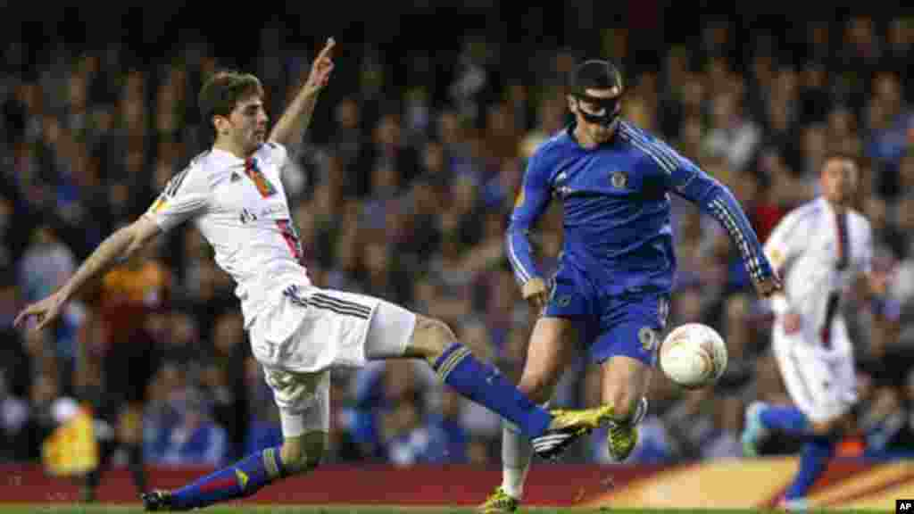 Chelsea's Fernando Torres, right, attempts to control the ball as Basel's Gaston Sauro attempts to tackle during their Europa League semifinal second leg soccer match, at Chelsea's Stamford Bridge stadium in London, Thursday, May 2, 2013. (AP Photo/Kirst