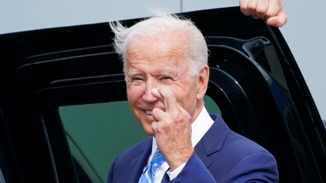US President Joe Biden crosses his fingers as he responds to a question about the short-term debt deal as he arrives Air Force One at O'Hare International Airport in Chicago, Oct. 7, 2021.