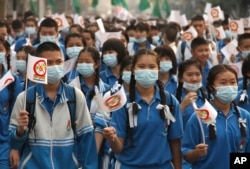 FILE - Thai schoolchildren wear masks and march on the street in a campaign to fight against the haze and smog in Chiang Mai province, northern Thailand, March 19, 2012.
