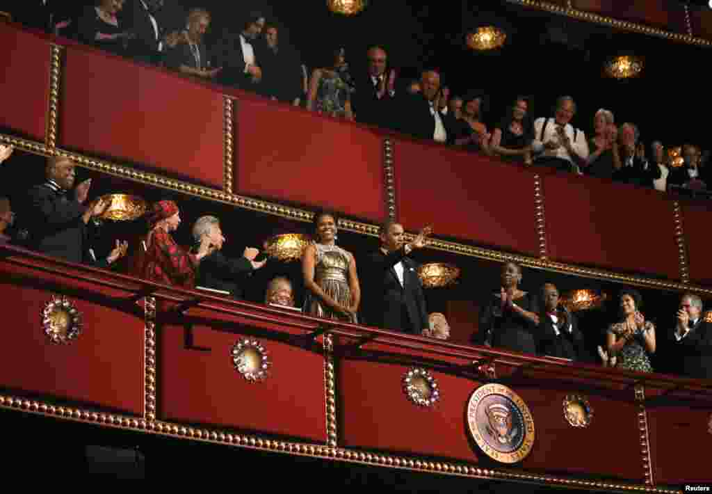 U.S. President Barack Obama and first lady Michelle Obama acknowledge the crowd on the balcony as they attend the 2012 Kennedy Center Honors at the Kennedy Center in Washington, December 2, 2012.
