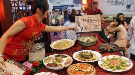 FILE - A saleswoman arranges a Taiwan's traditional food set designed to entertain guests during the Taiwan International Culinary Exhibition at the World Trade Center in Taipei, Taiwan.