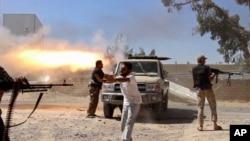 这幅由和米苏拉塔旅同行的人拍摄的业余视频截图显示,米苏拉塔旅民兵向的黎波里机场方向开火,试图从对立民兵派系手中夺取机场。(2014年7月26日)