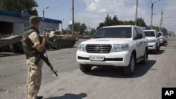 一名乌克兰政府军人7月31日在东乌克兰顿涅茨克地区的一个检查哨卡前,保护进入该地检查马航坠机事故的国际调查人员车队。