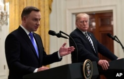 President Donald Trump, right, listens as Polish President Andrzej Duda, left, speaks during a joint news conference in the East Room of the White House in Washington, Sept. 18, 2018.