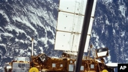 In this image provided by NASA this is the STS-48 onboard photo of the Upper Atmosphere Research Satellite (UARS) in the grasp of the RMS (Remote Manipulator System) during deployment, from the shuttle in September 1991. The satellite is 35 feet long, 15