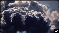 """In this July 1972 photo provided by the U.S. National Archives entitled """"Burning Discarded Automobile Batteries,"""" black clouds billow from smokestacks in Houston, Texas (file photo)."""