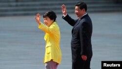 Presiden Korea Selatan Park Geun-Hye (kiri) dan mitranya dari China Presiden Xi Jinping melambaikan tangannya dalam lawatan Presiden Park Geun-Hye di Beijing, (27/6/2013).