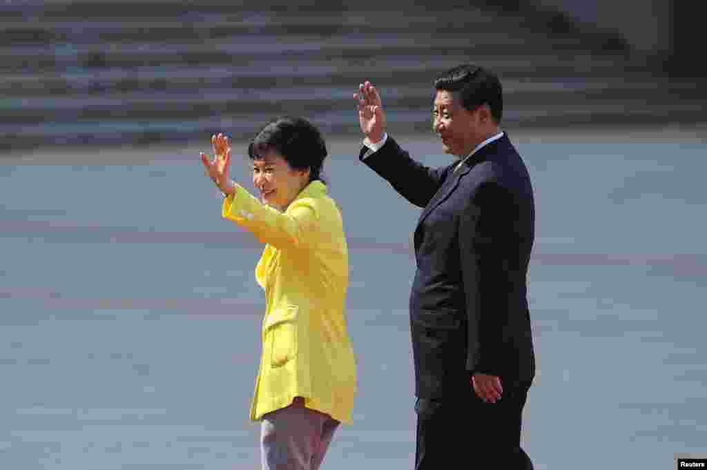 27일 중국 인민대회당 광장에서 열린 공식 환영 행사에서 박근혜 한국 대통령(왼쪽)이 시진핑 중국 공산당 국가주석과 함께 손을 흔들고 있다.