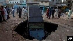 Warga Pakistan memeriksa kerusakan akibat ledakan bom sebelum subuh di Karachi, Pakistan (7/8). Sebuah bom yang nampaknya ditargetkan kepada seorang menteri pemerintahan provinsi, dilaporkan telah menewaskan 11 orang di wilayah ini.
