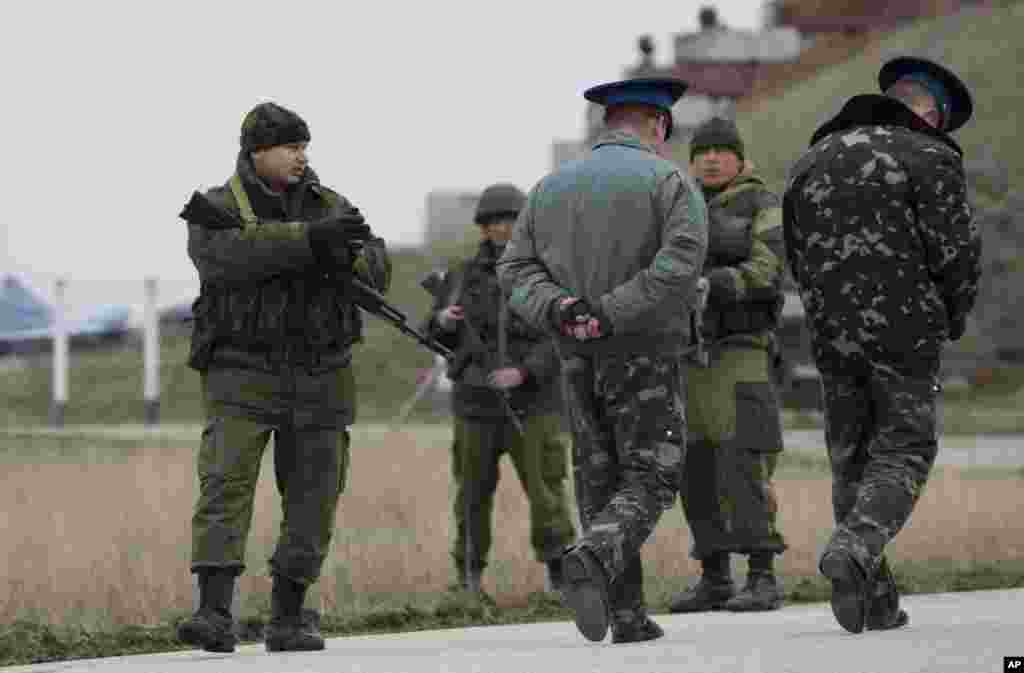 Ukrainian officers arrive for talks as Russians guard at the Belbek air base, outside Sevastopol, Ukraine, March 4, 2014.