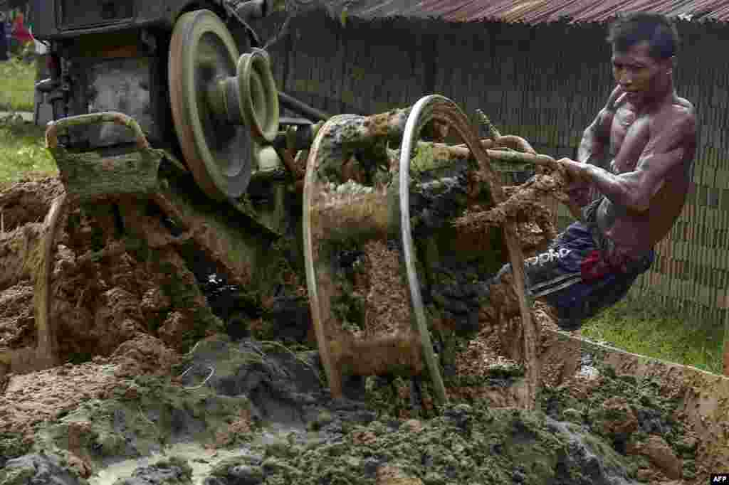 A man mixes materials to make bricks at a brick factory on the outskirts of Kajhu, Aceh province, Indonesia.