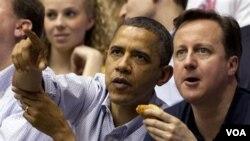 Presiden AS Barack Obama dan tamunya, PM Inggris David Cameron menonton pertandingan bola basket perguruan tinggi AS di Ohio (13/3).
