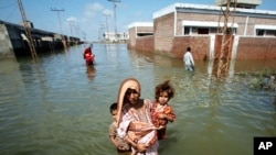 A woman escapes to higher ground from her flooded village in the Mirpur Khas district of Pakistan's Sindh province.