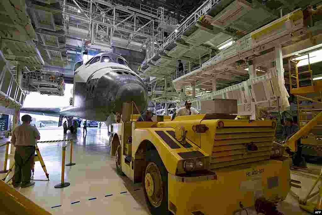 """A """"towback"""" vehicle positions space shuttle Discovery between the extensible work platforms of Orbiter Processing Facility-2 at NASA's Kennedy Space Center in Florida, March 9, 2011. (NASA)"""
