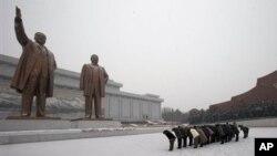 Warga Korea Utara memberi hormat kepada patung mendiang pemimpin Korea Utara, Kim Il-sung dan Kim Jong-il di Mansu Hill, saat salju menyelimuti Pyongyang, Korea Utara (21/12). Media setempat mengabarkan wisatawan Amerika, Bae Jun Ho ditahan di negara itu atas tuduhan melakukan tindak kejahatan.
