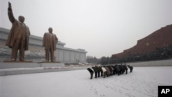 تعظیم در مقابل مجسمه کیم ایل سونگ و کیم جونگ ایل، رهبران سابق کره شمالی