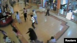 FILE - Shoppers flee during an attack by gunmen, inside the Westgate shopping mall in this still frame taken from video footage by security cameras inside the mall in Nairobi, Kenya, released on Oct. 17, 2013.