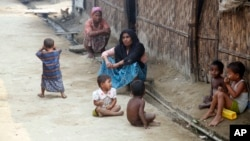 Rohingya Muslims sit on the ground at Da Paing camp for Muslim refugees in north of Sittwe, Rakhine State, western Myanmar, April 2, 2014.