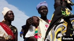 FILE - A woman carries a baby as she talks with other women talk at a food distribution center in Minkaman, Lakes State, South Sudan, June 27, 2014.