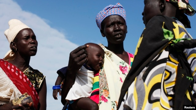 FILE - A woman carries a baby as she talks with other women talk at a food distribution center in Minkaman, Lakes State, South Sudan.