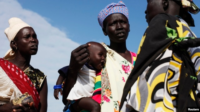 A woman carries a baby as she talks with other women talk at a food distribution center in Minkaman, Lakes State, South Sudan, June 27, 2014.