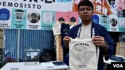 香港眾志主席林朗彥展示被中國當局禁印該黨標誌的布袋。(美國之音湯惠芸)