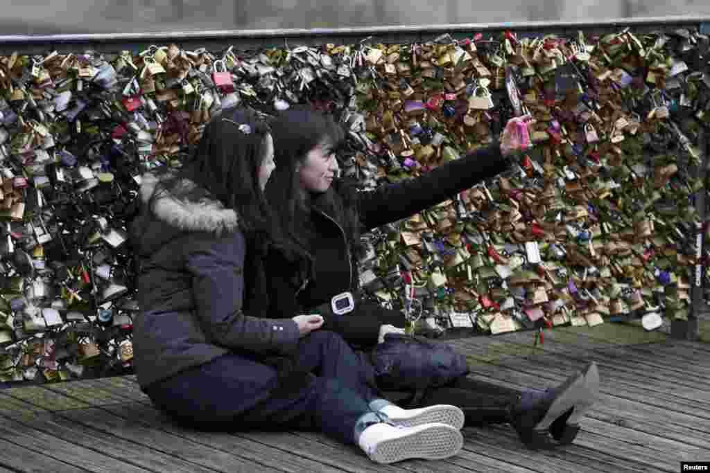 اس موقع پر پیرس میں دو سیاح تصویر بنوا رہے ہیں