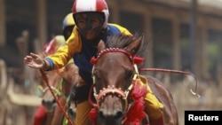 Seorang joki anak-anak melambaikan tangannya setelah memenangkan pacuan kuda di luar kota Bima, Nusa Tenggara Barat. (Reuters/Beawiharta)