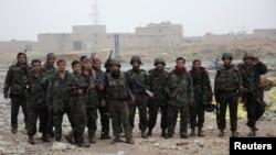 Tentara Suriah yang setia kepada Presiden Bashar al-Assad berpose dengan senjata mereka di kota Naqaren, Aleppo, setelah mengklaim berhasil menguasai kembali wilayah itu pada 13/1/ 2014.