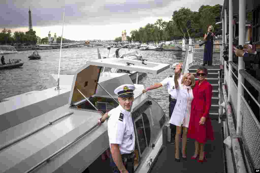 U.S. First Lady Melania Trump, right, and French president's wife Brigitte Macron wave after a boat trip down the River Seine in Paris.