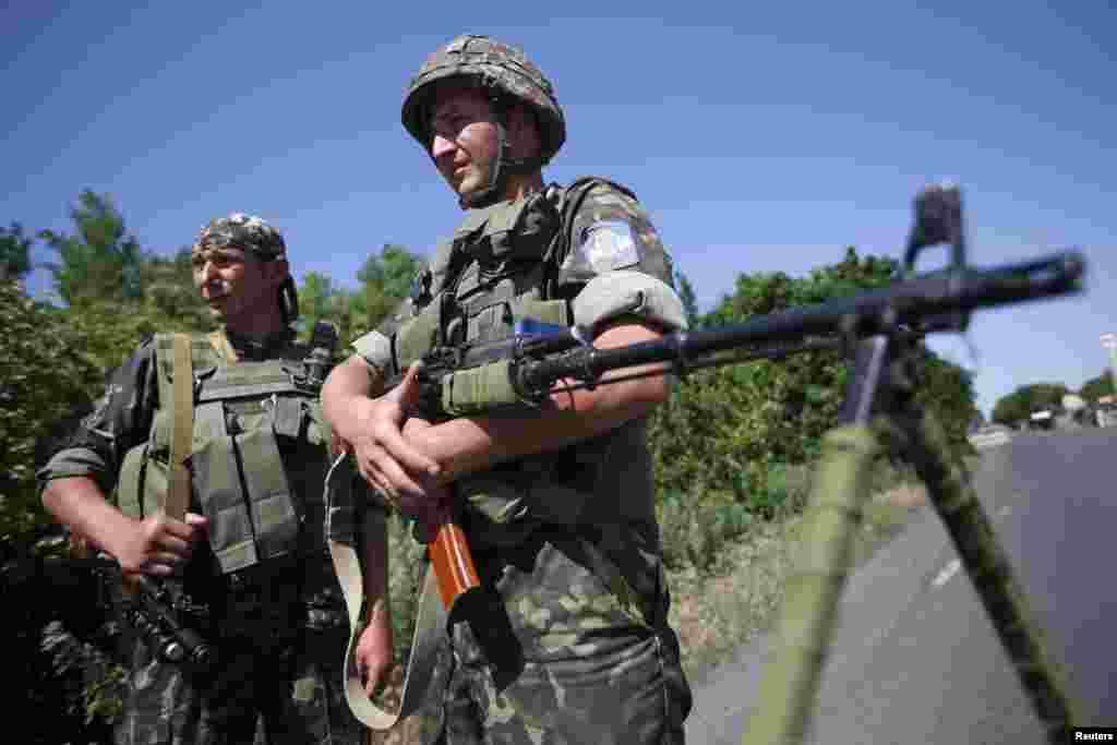 Ukrainian servicemen stand guard at a checkpoint near the town of Amvrosievka, in Donetsk region, Ukraine, June 5, 2014.