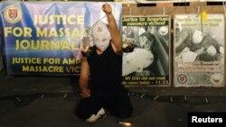Một nghệ sĩ người Philippines đeo mặt nạ, cầm một cái cân đang cháy, biểu thị cho công lý vào kỷ niệm năm thứ nhì vụ xử cuộc thảm sát Maguindanao, 23/11/11