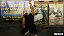 Seorang seniman Filipina mengangkat replika timbangan, meminta keadilan atas pembunuhan para jurnalis dan di Klub Pers Nasional, Manila. (Foto: Dok)