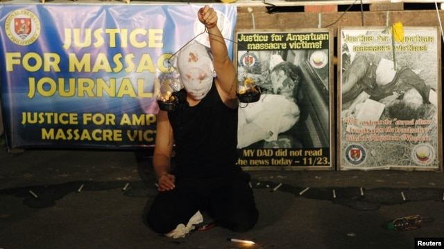 "A masked Filipino artist holds up a replica of a burning weighing scale signifying justice to commemorate the 2nd year anniversary of the ""Maguindanao Massacre"" at the National Press Club compound in Manila, November 23, 2011."