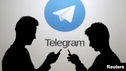 FILE - Two men pose with smartphones in front of a screen showing the Telegram messenger app logo in a picture illustration taken Nov. 18, 2015.