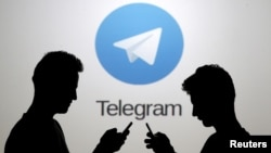 FILE - Two men pose with smartphones in front of a screen showing the Telegram logo in this picture illustration taken in Zenica, Bosnia and Herzegovina, Nov. 18, 2015.