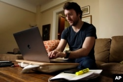 FILE - Journalist Michael Weiss works on his laptop in his apartment on New York's Upper West Side, Dec. 8, 2017.