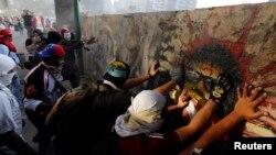 4일 베네수엘라 수도 카라카스의 알타미라 광장에서 반정부 시위가 계속된 가운데, 시위대가 벽을 무너뜨리고 있다.
