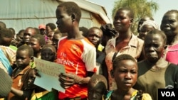 Refugees stand with a placard that reads: #ImmediateRelocation. Many refugees want to go to a settlement camp in Adjumani, but officials say these are full. ( Photo: Lizabeth Paulat for VOA)