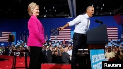 FILE - President Barack Obama points to Democratic presidential candidate Hillary Clinton during a Clinton campaign event in Charlotte, N.C., July 5, 2016.
