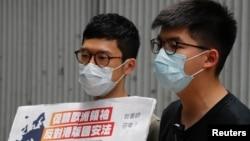 Aktivis Pro-demokrasi Hong Kong, Nathan Law dan Joshua Wong memberikan keterangan kepada media dalam menanggapi undang-undang keamanan nasional di Hong Kong, 3 Juni 2020. (REUTERS / Tyrone Siu)